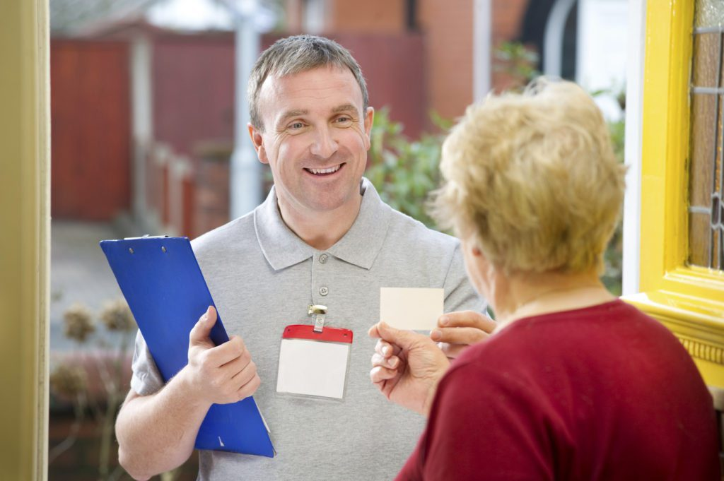 Smiling salesman shows senior woman his card